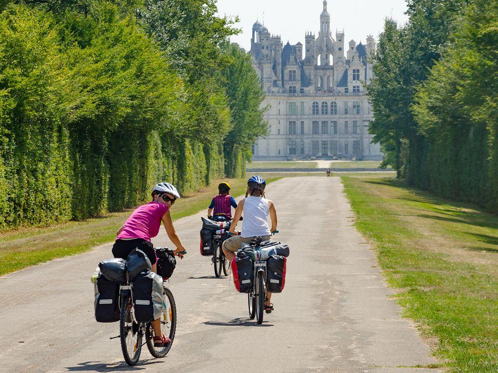Cyclists cycling towards a chateau